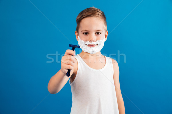 Smiling young boy in shaving foam showing razor Stock photo © deandrobot