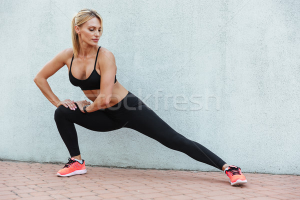 Amazing strong young sports woman make sports exercises Stock photo © deandrobot