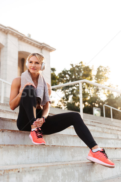 Beautiful strong young sports woman sitting on steps Stock photo © deandrobot