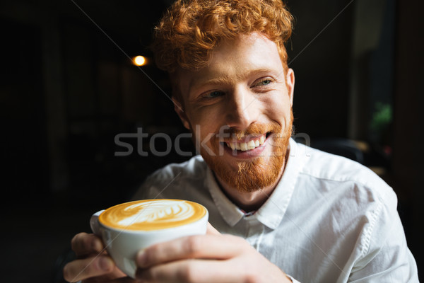 Portrait of young readhead bearded man with charming smile in wh Stock photo © deandrobot