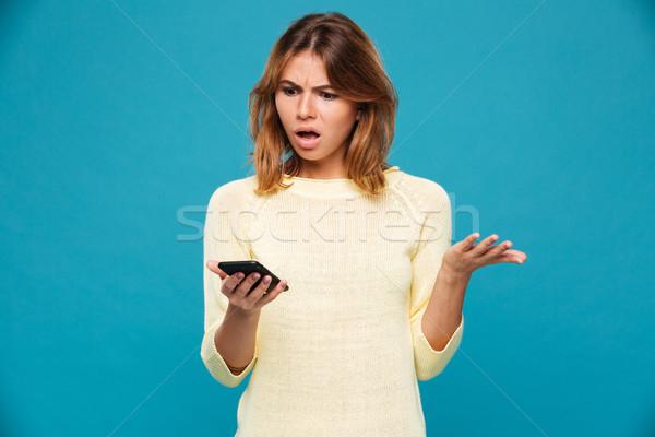 Conmocionado mujer suéter mirando azul Foto stock © deandrobot