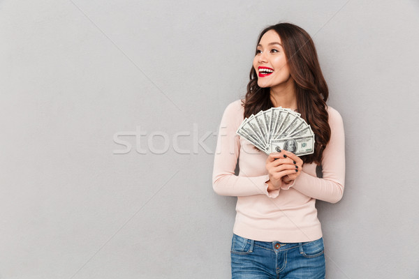 Photo of successful brunette adult girl holding fan of 100 dolla Stock photo © deandrobot