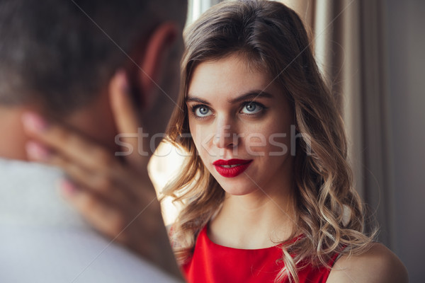 Serious woman flirting and hug her man while posing near window Stock photo © deandrobot