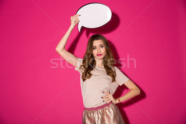 Displeased young woman holding speech bubble over head. Stock photo © deandrobot