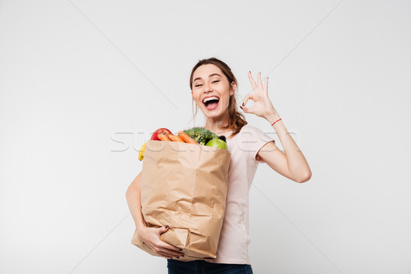 Portrait of a happy satisfied girl holding grocery bag Stock photo © deandrobot