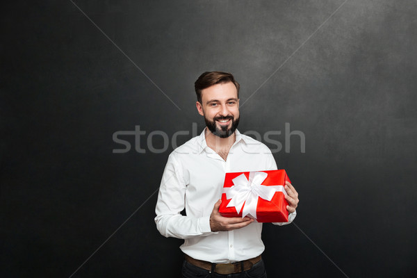 Portrait of happy bearded man holding red gift box and looking a Stock photo © deandrobot