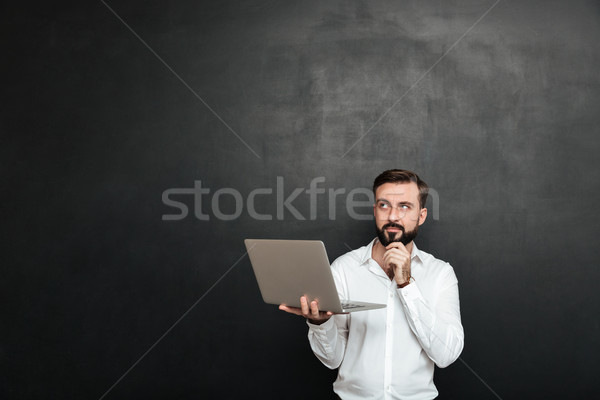 Image of concentrated unshaved guy looking upward and touching h Stock photo © deandrobot