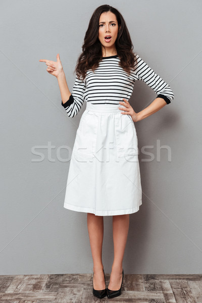 Full length portrait of a frowning woman Stock photo © deandrobot