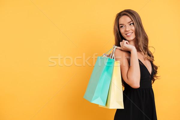 Derűs fiatal hölgy fekete ruha tart bevásárlótáskák Stock fotó © deandrobot