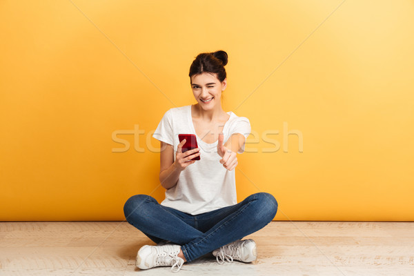 Portrait of a playful young woman holding mobile phone Stock photo © deandrobot