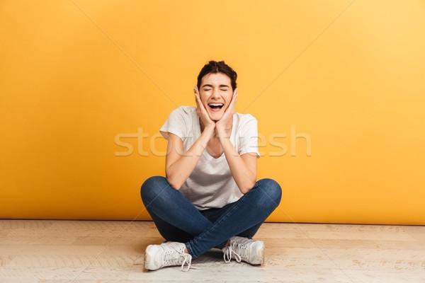 Ritratto eccitato seduta gambe incrociate piano Foto d'archivio © deandrobot