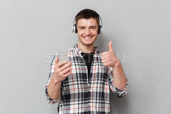 肖像 満足した 若い男 音楽を聴く ヘッドホン ストックフォト © deandrobot
