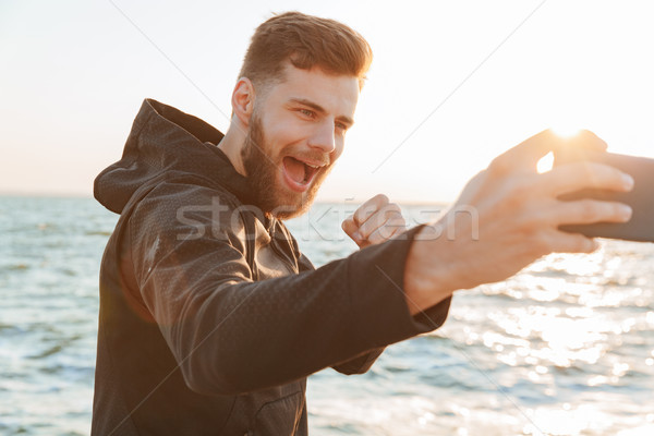 Happy young sportsman taking selfie with mobile phone Stock photo © deandrobot