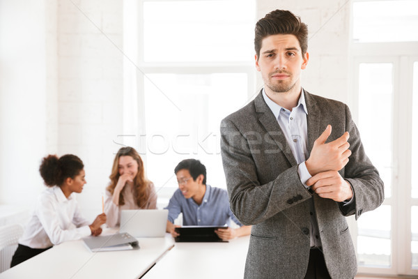 Confident young man standing at the table Stock photo © deandrobot