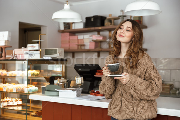 Gorgeous woman in sweater looking aside and smiling, while holdi Stock photo © deandrobot