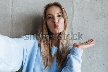 Pensive brunette woman in sweater holding chin and looking up Stock photo © deandrobot