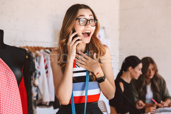 Cheerful young woman clothes designer at the atelier Stock photo © deandrobot