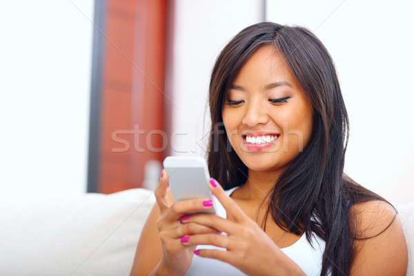Beautiful young asian woman text messaging with her smart phone at home Stock photo © deandrobot