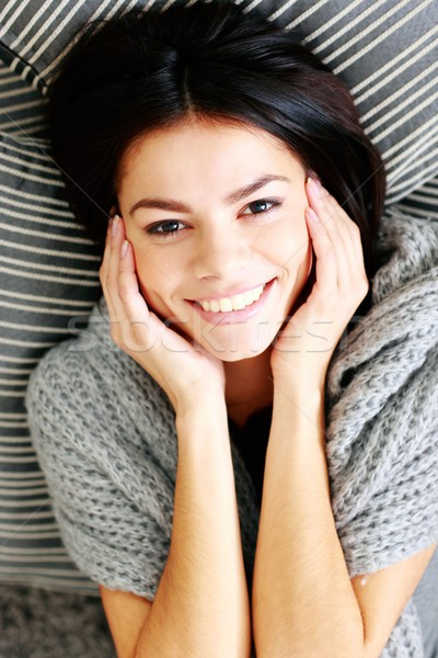 Happy smiling woman lying on the floor with pillows. View from above Stock photo © deandrobot