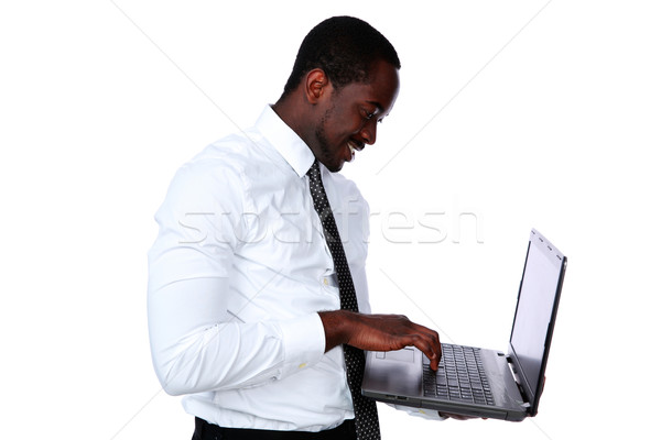 Happy african man standing and using laptop over white background Stock photo © deandrobot