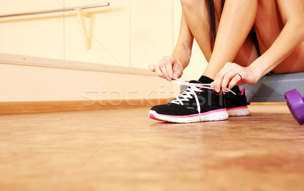 Young fit woman tying her shoelaces at gym Stock photo © deandrobot