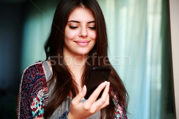 Happy woman using smartphone at home Stock photo © deandrobot
