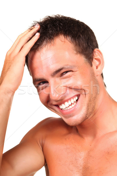 Stock photo: Closeup of a happy young man looking at camera and touching his hair
