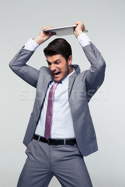 Angry businessman smashing his laptop Stock photo © deandrobot