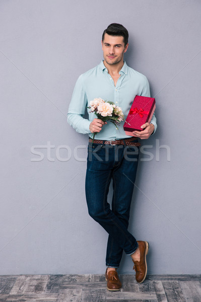 Happy young man holding gift box and flowers Stock photo © deandrobot