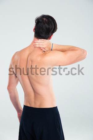Rear view portrait of a muscular man with neck pain Stock photo © deandrobot