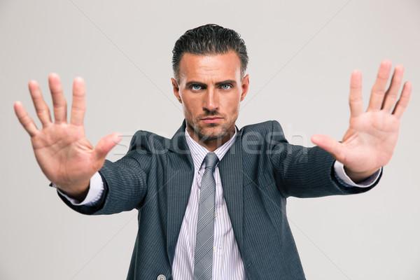 Confident businessman showing stop gesture Stock photo © deandrobot