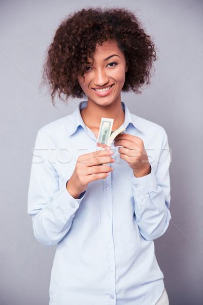Smiling afro american woman holding money Stock photo © deandrobot