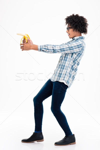 Funny afro american man aiming from banana Stock photo © deandrobot