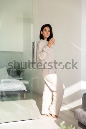 Beautiful sensual barefooted female in white bathrobe sitting on bathtub  Stock photo © deandrobot
