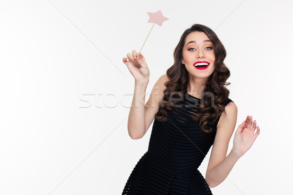 Cheerful beautiful curly young woman posing with magic wand Stock photo © deandrobot