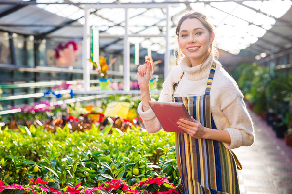 Smiling woman gardener using tablet in greenhouse  Stock photo © deandrobot