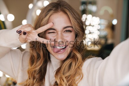 Smiling charming young woman in black dress with closed eyes  Stock photo © deandrobot