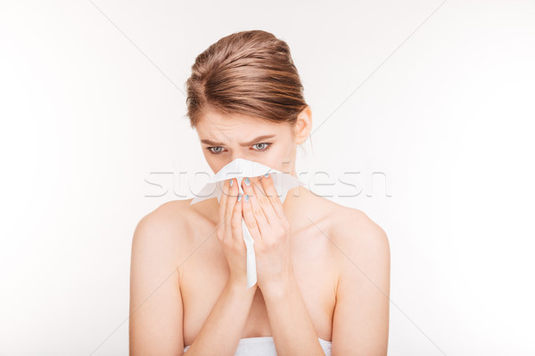 Sad ill young woman sneezing and using paper handkerchief  Stock photo © deandrobot