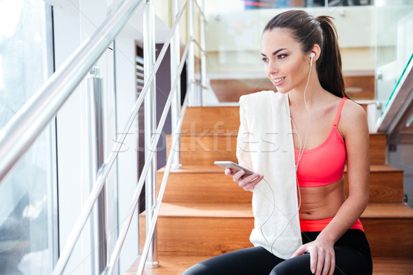 Stock photo: Happy charming sportswoman listening to music from smartphone in gym