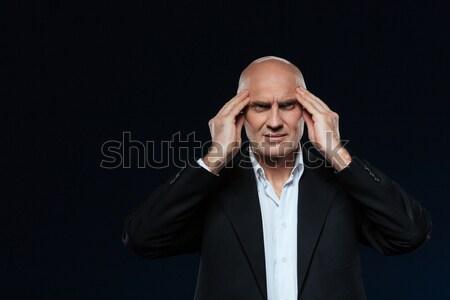 Maduro empresário dor de cabeça em pé preto fundo Foto stock © deandrobot