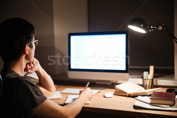 Back view of man reading information from blank screen computer  Stock photo © deandrobot