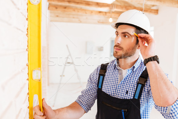 Close-up prtrait of a smart concentrated builder indoors Stock photo © deandrobot