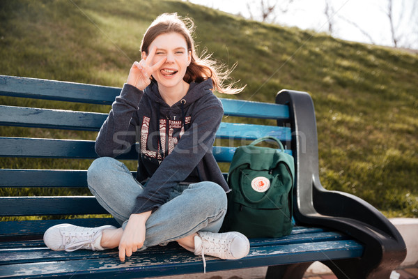 Funny woman winking and showing peace sign sitting on bench Stock photo © deandrobot