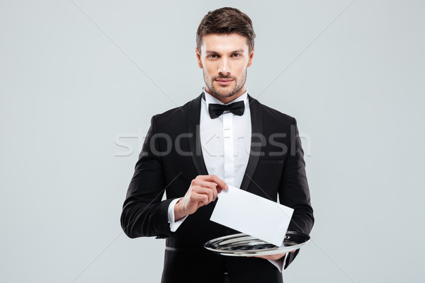 Stock photo: Handsome young waiter in tuxedo holding tray with blank card
