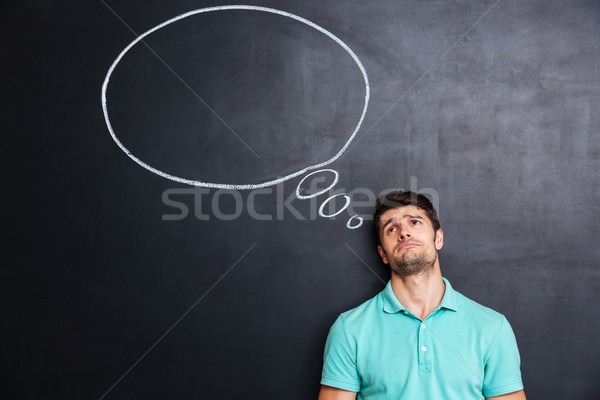 Unhappy despaired man over blackboard background with speech bubble Stock photo © deandrobot