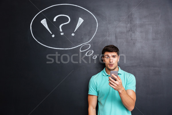Amazed puzzled young man using cell phone over chalkboard background Stock photo © deandrobot