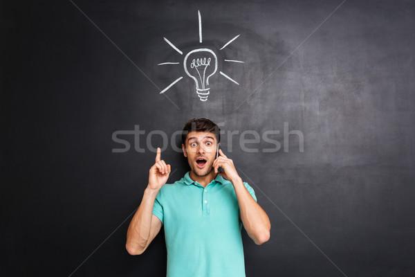 Maravilhado homem falante celular idéia moço Foto stock © deandrobot