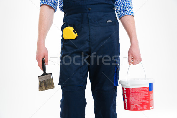 Closeup of man painter holding paint can and brush Stock photo © deandrobot