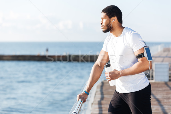 Sportsman listening to music and drinking water on pier Stock photo © deandrobot