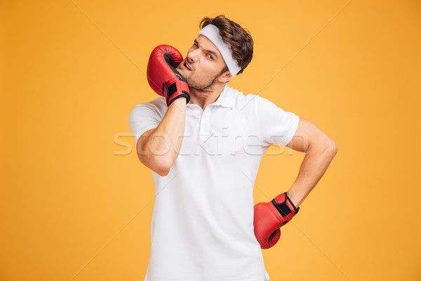 Young man boxer in red gloves standing and warming up Stock photo © deandrobot